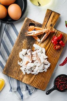 スペイン語またはタイ語のオムレツの材料、新鮮な赤唐辛子、茶色と白のカニ肉、レモン、チェダーチーズ、卵セット、白い背景、上面図フラットレイ
