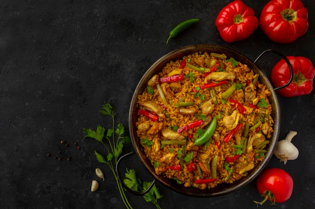 Испанский рис паэлья с курицей на темном фоне