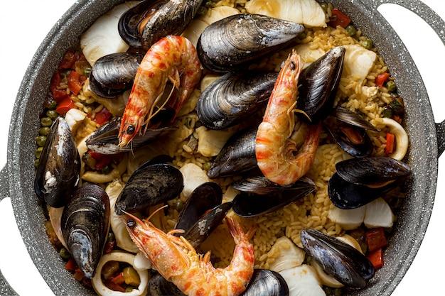 Испанская паэлья с морепродуктами на традиционной сковороде. крупный план