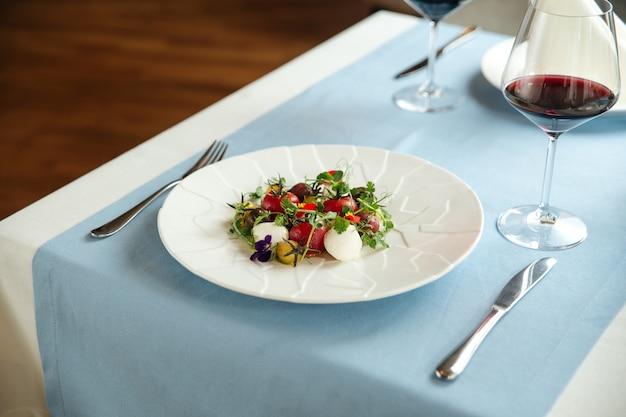 Салат из очищенных помидоров с зеленью на синем сервированном столе