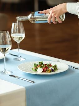 화이트 와인을 붓는 웨이터의 손으로 스페인 껍질을 벗긴 토마토 샐러드