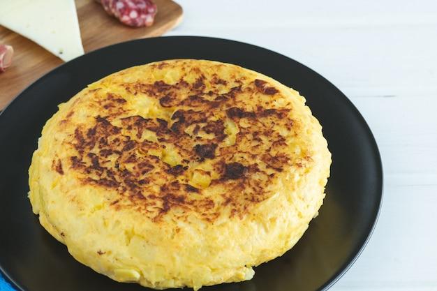 Испанский картофельный омлет на черной тарелке на белом фоне.