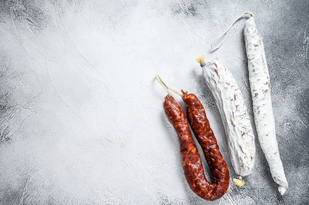 Spanish salami, fuet and chorizo sausages on a kitchen table. white background. top view. copy space.