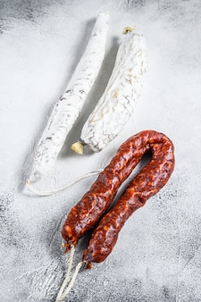 Spanish salami, fuet and chorizo sausages on a kitchen table. white background. top view.
