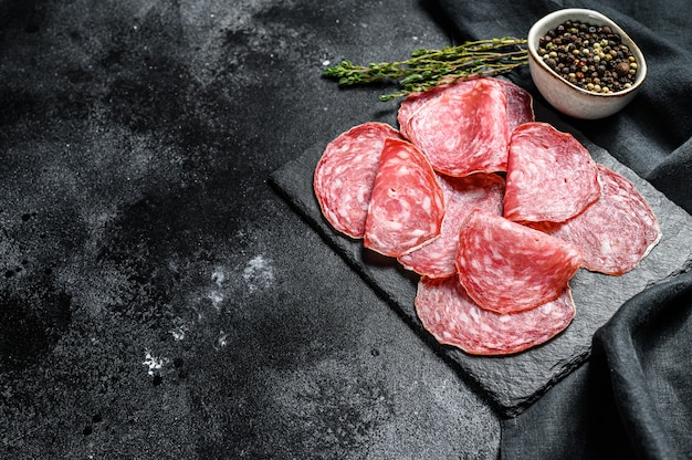 Spanish salami salchichon on a black chopping board. black background. top view. copy space