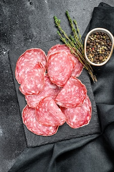 Spanish salami salchichon on a black chopping board. black background. top view