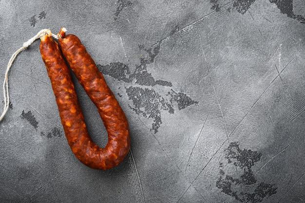 Испанская колбаса салями чоризо на серой текстурированной поверхности, вид сверху с копией пространства.