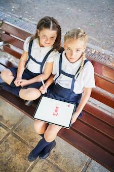 Испанские школьницы рисуют на планшете в парке и смотрят в камеру