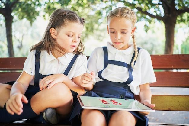 Испанские школьницы рисуют на планшете в парке