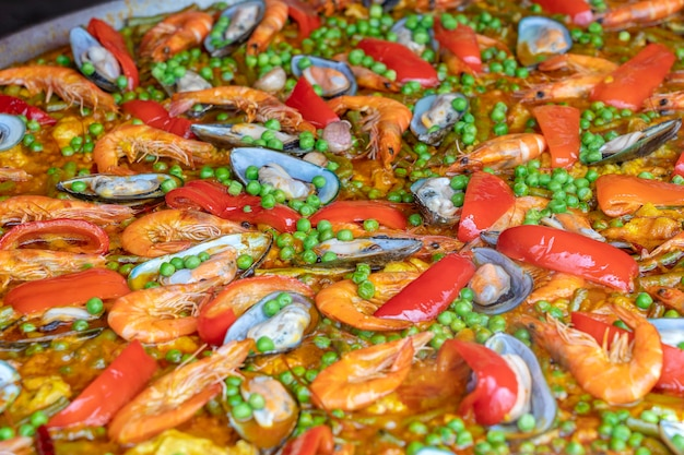 Spanish seafood paella in fry pan with mussels, shrimps and vegetables. seafood paella background, close up, traditional spanish rice dish