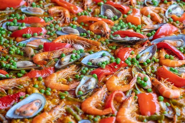 ムール貝、エビ、野菜とフライパンでスペインのシーフードパエリア。シーフードパエリアの背景、クローズアップ、伝統的なスペインの米料理