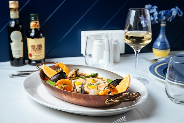 Spanish seafood paella in a pan with glass of wine