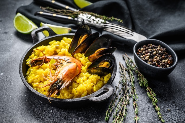 The spanish seafood paella in a pan with prawns, shrimps, octopus and mussels.  black background. top view.