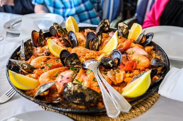 Испанское блюдо из паэлья с морепродуктами и свежими креветками, креветками, мидиями, кальмарами, осьминогом и морскими гребешками. подается в сковороде. вид сверху. ресторан