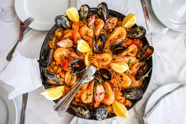 Spanish seafood paella rice dish with fresh shrimp, scampi, mussels, squid, octopus and scallops served in pan.  top view. restaurant