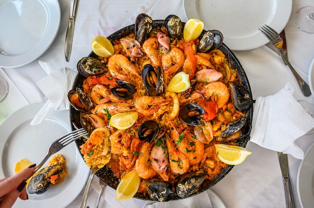 Spanish seafood paella rice dish with fresh shrimp, scampi, mussels, squid, octopus and scallops served in pan.  the waiter puts a portion on the plate. top view. restaurant