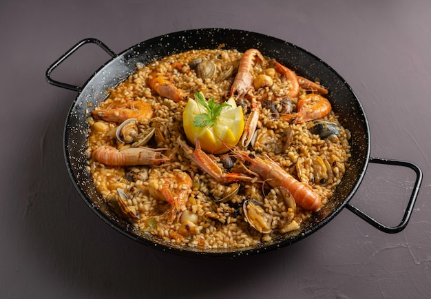 Spanish seafood paella with rustic dark background