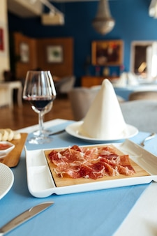 Spanish sliced pork jamon with red wine on the restaurant table
