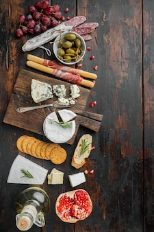 Spanish snacks, meat cheese, herbs set, on dark wooden table, flat lay