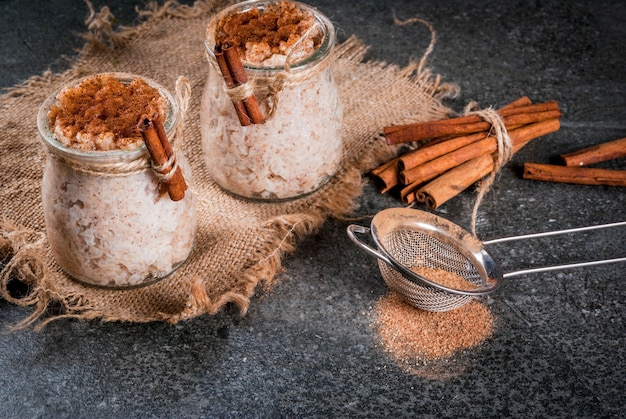 Spanish, south american, mexican dessert. sweet porridge, rice pudding. arroz con leche. in portioned jars, decorated with cinnamon and sugar. on a dark stone table. copy space