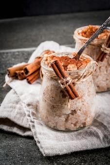 Spanish, south american, mexican dessert. sweet porridge, rice pudding. arroz con leche. in portioned jars, decorated with cinnamon and sugar. on a dark stone table. copyspace
