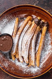 スペインのタパスチュロスと砂糖とチョコレートソース。闇