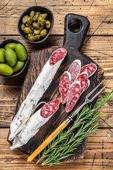 Spanish tapas fuet salami sausage slices with olives and rosemary on a wooden board.