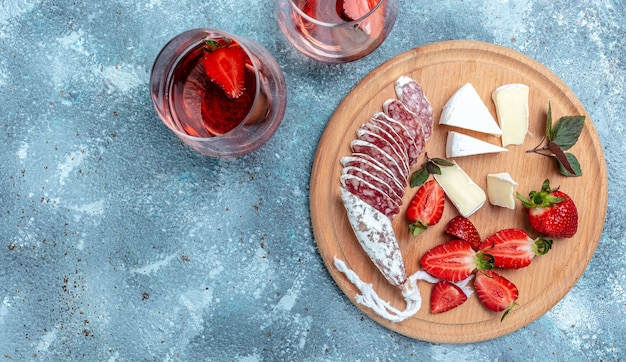 Spanish tapas sliced sausages fuet and camembert cheese, strawberries and glass rose wine on a wooden cutting board on blue background. banner, menu recipe place for text, top view.