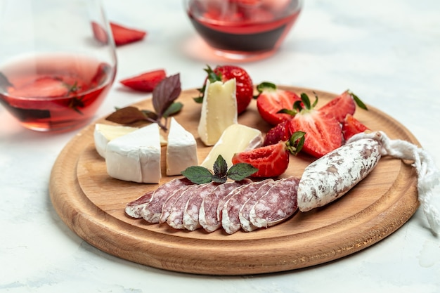 Spanish tapas sliced sausages fuet and camembert cheese, strawberries and glass rose wine on a wooden cutting board.