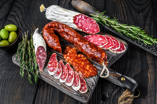 Spanish tapas sliced sausages salami, fuet and chorizo on a wooden cutting board. black wooden background. top view.