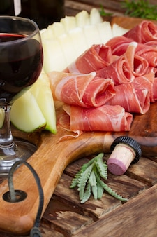 Spanish tapas  - slices of cured pork ham jamon with melon and wine
