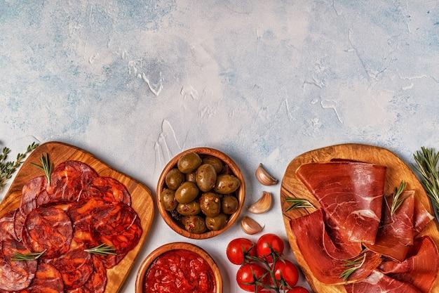 Spanish tapas with chorizo, jamon, picnic table, top view