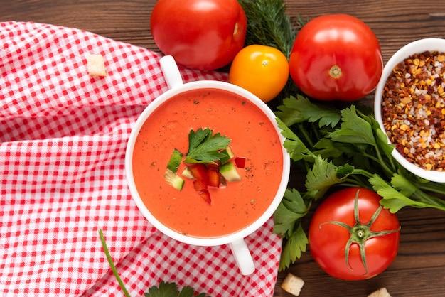 木製の背景にさまざまなスパイスやハーブを使ったフレッシュトマトから作られたスペインのトマトガスパチョスープ。