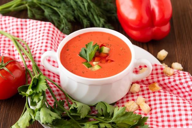 다양 한 향신료와 허브 나무 배경에 신선한 토마토로 만든 스페인 토마토 가스 파초 수프.