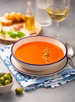 Spanish traditional dish. cold, veggie soup made from tomatoes, peppers, garlic and olive oil with tabasco sauce in a white plate on a napkin. white wine in a glass, olives and sliced white bread