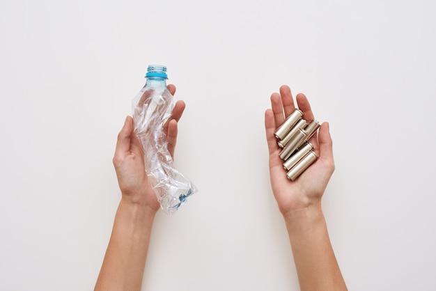 쓰레기를 분리하십시오. 두 사람의 손이 플라스틱과 분리된 배터리를 들고 있습니다.