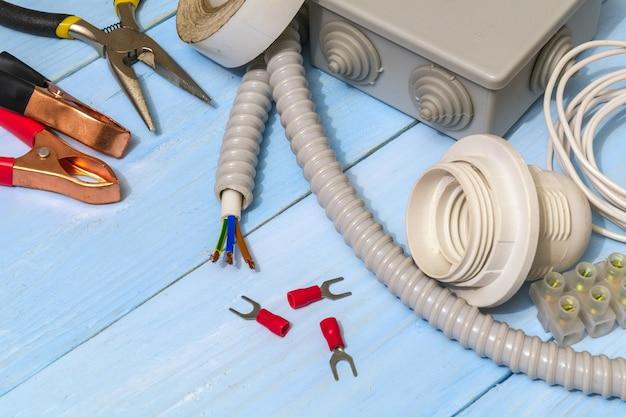 修理前に準備された電気用の青いボード上のスペアパーツとツール