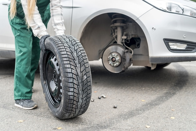 Spare wheel with worker's hands close up Premium Photo