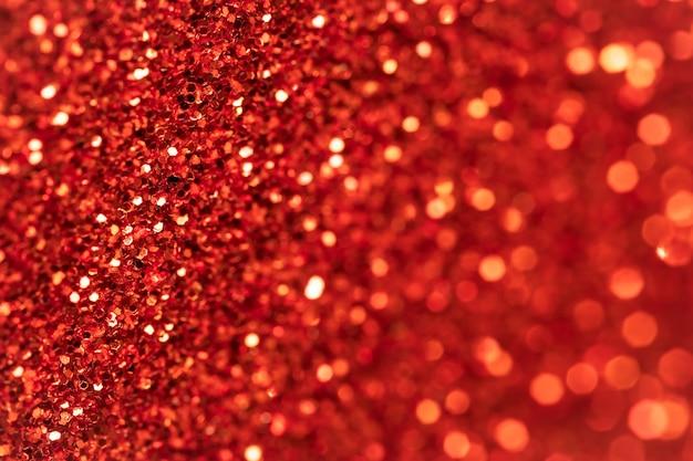 きらめく赤いテクスチャの背景。キラキラテキスタイル表面。お祝いの抽象化。スパンコール付きの光沢のある生地。ライト付きホリデーアートデザイン。
