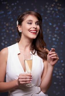 きらめく壁とシャンパンを持つ女性