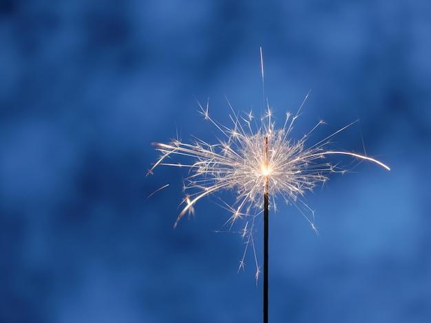 Sparkler on blue festive background