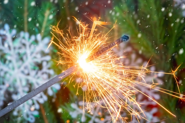 Sparkler and bokeh of christmas tree on background