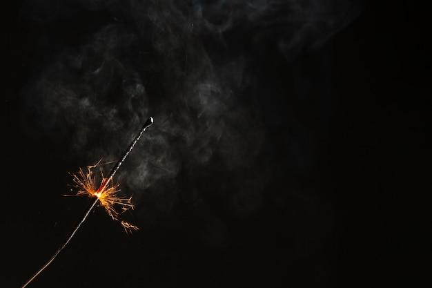Sparkler flaming on black background