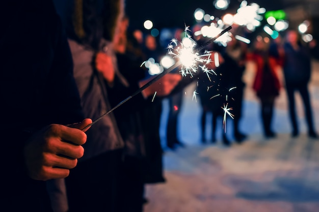 Sparkler in hands of people on holiday with sparks