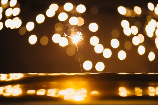 Sparkler e luci su superficie riflettente