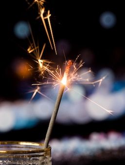 Sparkler in transparent glass with bokeh light background