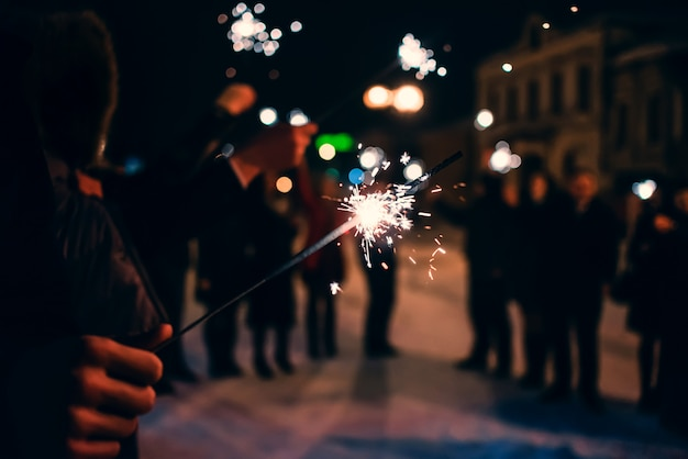 Sparkler with sparks in man hand at the festival