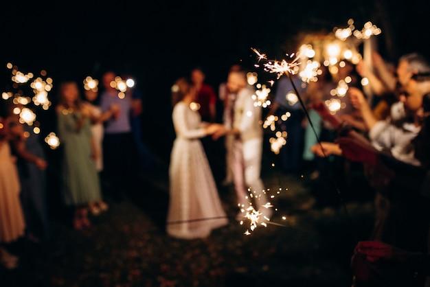 結婚式の線香花火、背景に新婚夫婦のカップル