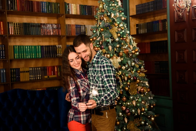 Sparklers and a kiss for christmas! young beautiful kisser and burning sparklers. loving couple  in christmas decorated room.