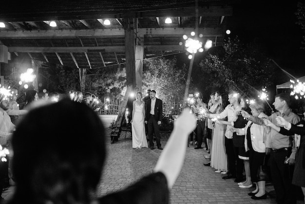 Sparklers at the wedding of the newlyweds in the hands of joyful guests